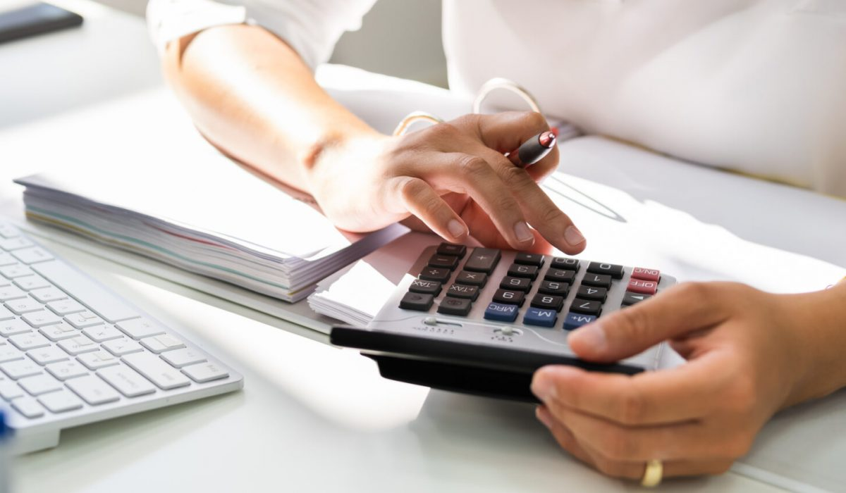Lady Calculating Invoice. Chartered Accountant With Calculator